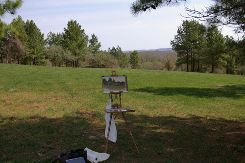 A photo showing a plein air painting setup in a field with Jullian half-box easel.