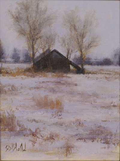 A small dark barn in a snowy landscape with dry grasses and bare trees.