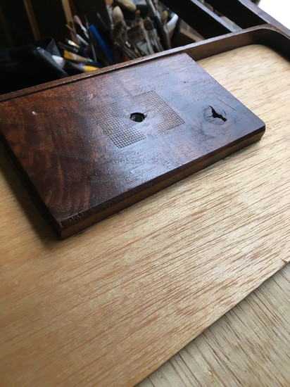 A wood support on the bottom of a pochade box houses a t-nut to which a quick release mounting plate is attached
