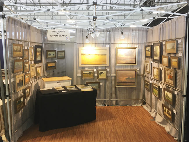 An indoor art fair booth with lighting, drapes and flooring